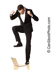 young and attractive furious businessman in black suit, destroying his laptop using his foot