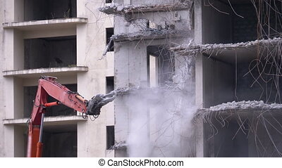 Destroying Old Concrete Building Using Mechanical Arm of Bulldozer on Construction Site. Demolition of the old multi flat house. Twisted rebars, broken pillars and scattering concrete dust. Bucket Excavator working producing rubbish in a demolition site.