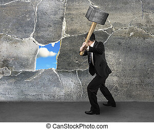 Destructing the wall with a large hammer - businessman ...