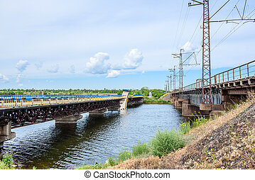 Destruction of bridge structures across the river with the collapse of sections into the water