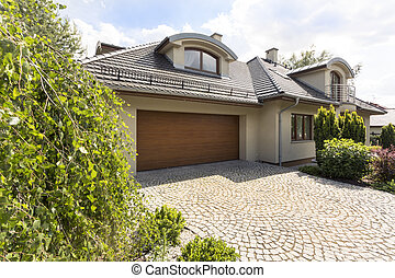 Detached house exterior with cobblestone driveway