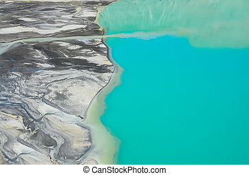 Detail aerial view of river flowing into mountain lake -...