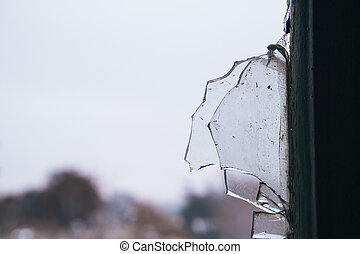 Detail of a broken glass of a window of an abandoned ...