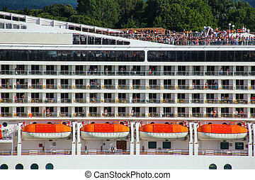 Detail of a crouded cruise ship moving through San Marco canal in Venice, Italy
