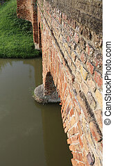 detail of a medieval bridge made of red brick