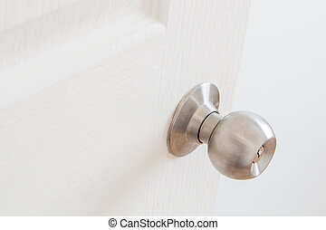 Detail of a metallic knob on white door , tainless steel round b