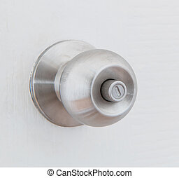 Detail of a metallic knob on white door , tainless steel ...