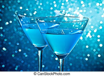 detail of a pair of glasses of blue cocktail on light blue tint bokeh background
