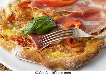 detail of a pizza with ham and basil