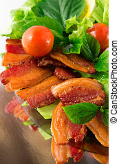Detail of a plate of fried bacon and  cherry tomatoes