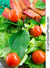 Detail of a plate with cherry tomatoes, herbs and bacon
