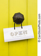 Detail of a vintage brass doorknob with open sign on a bright yellow wooden door