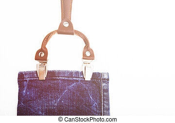 Detail of a white suspenders on vintage jeans