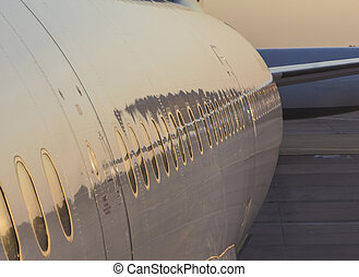 aircraft with reflection of sunset in window and body