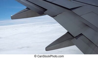 detail of an airplane wing flying over clouds
