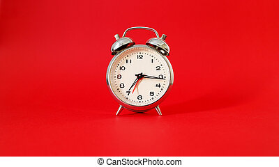 Detail of an alarm clock with red background