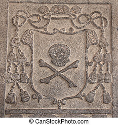 Detail of an ancient carved stone frame with with skull and bones