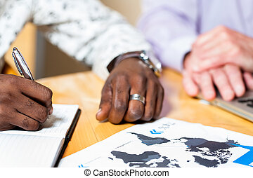 Detail of black business man signing documents.