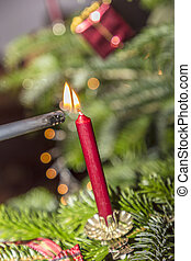 burning red candle at the christmas tree