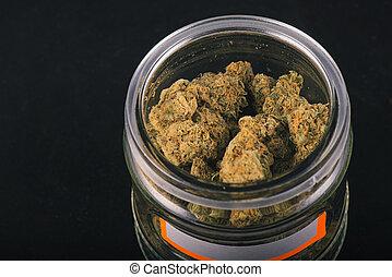 Detail of cannabis buds (grape god strain) on a glass jar...