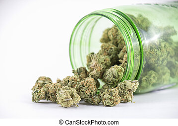 Detail of cannabis buds (ob reaper strain) on green glass jar isolated on white - medical marijuana concept