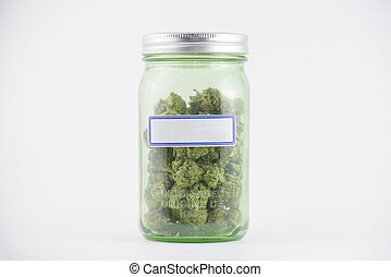 Detail of cannabis buds on green glass jar isolated on white