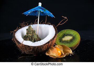 Detail of cannabis buds with fresh coconut and kiwi over ...