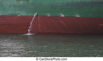 Side of cargo ship. Water coming out of side. Toronto, Ontario, Canada.