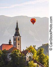 Detail of Catholic Church in Bled Lake, Slovenia with Hot Air Balloon Flying at Sunrise