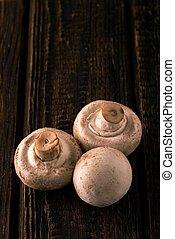 Detail of champignon mushrooms on worn wooden board