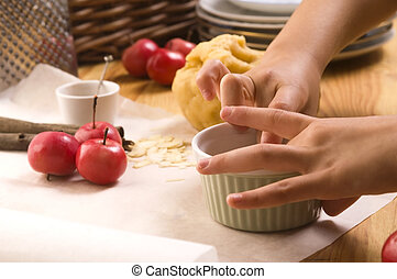 Detail of child hands making apple pie