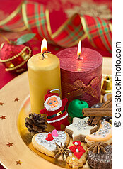 Detail of Christmas cookies with candles on golden plate