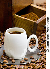 detail of coffee mill with coffee beans and cup of coffee