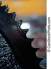 Detail of black, cogged wheel