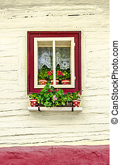 Detail of colorful window with flowers on old traditional house