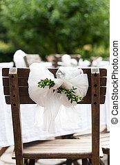 Detail of countryside wedding decoration: textile chair bow with myrtle branches