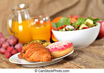 Detail of croissant and donuts, orange juice and fresh salad - breakfast on wooden table