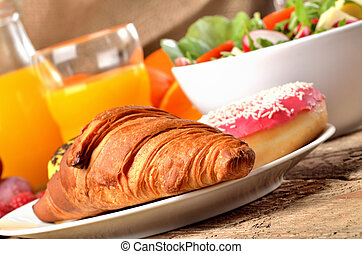 Detail of croissant, orange juice and fresh salad - breakfast on wooden table
