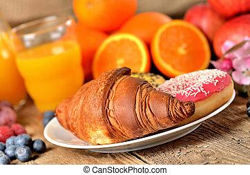 Detail of croissant, orange juice, blueberries, raspberries, apples and donuts - sweet breakfast on wooden table