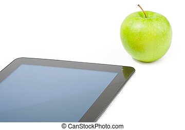 detail of digital tablet pc near green apple on white background, concept of learn new technology