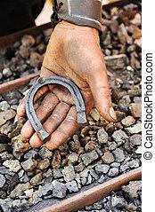 Detail of dirty hand holding horseshoe - blacksmith