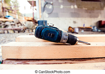 Detail of drill laying on wooden beams on site - Close up of...