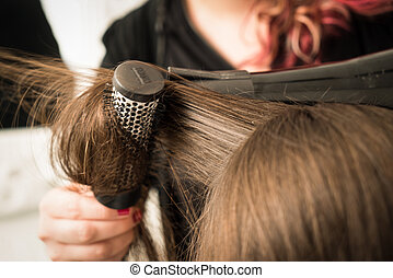 Detail of drying hair with hair dryer and brush.