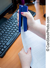 Detail of female hands holding a stapler and filling it with the staples. Hands holding stapler and paper. Close up of a woman hands and holding a blue stapler in her hand. Concept of personal assistant work