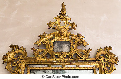 Detail of gilded frame of an antique mirror.