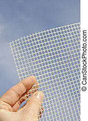 Detail of glass-fiber mesh in hand - reinforcing material for insulation