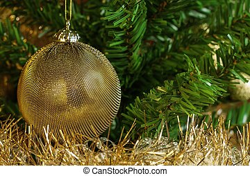 Detail of golden decoration on the christmas tree with gold chain