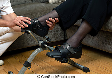 Detail of hands holding foot in stationary rehabilitation pedals.