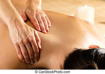 Detail of hands massaging female back.