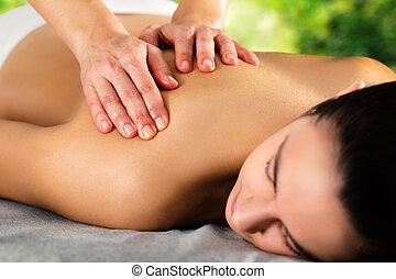 Detail of hands massaging female shoulder.